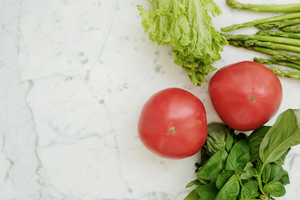 Growed Indoors Tomatoes with leafy greens and herbs on cutting board